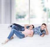 愉快的年轻夫妇,说谎在地板上,看家具彼此和梦想为一栋新的公寓 嘲笑 免版税库存图片