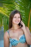 愉快的年轻女人在棕榈树下谈话在智能手机 库存照片