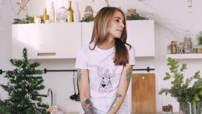 愉快的年轻女人坐厨房用桌 圣诞节内部 股票视频