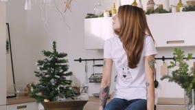 愉快的年轻女人坐厨房用桌 圣诞节内部 股票录像