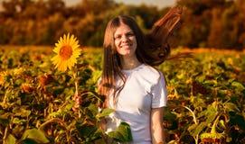 愉快的年轻女人夏天画象帽子的有在向日葵领域的长发的 库存图片