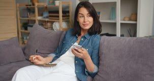 愉快的年轻女人文字的慢动作在看智能手机的笔记本的 股票录像
