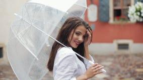 愉快的年轻女人跳舞和有乐趣与伞在老城市的街道上 摆在美好的firl看和 股票视频