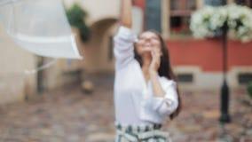 愉快的年轻女人跳舞和有乐趣与伞在老城市的街道上 摆在美好的firl看和 股票录像