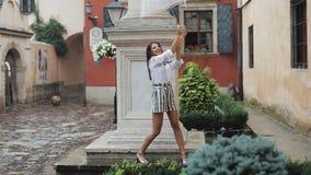 愉快的年轻女人跳舞和有乐趣与伞在老城市的街道上 摆在美好的firl看和 影视素材