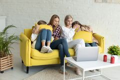 愉快的年轻女同性恋的加上便服的女儿在家一起坐黄色沙发,退出了家庭 免版税库存图片