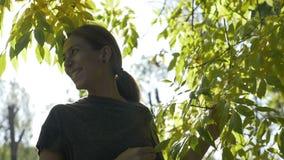 愉快的年轻女性佩带的体育在一温暖的秋天天给微笑和享用从一个公园的黄色和绿色叶子穿衣 股票录像