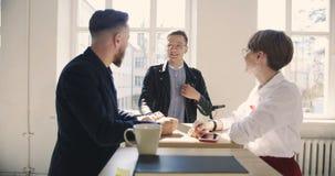 愉快的年轻女性和男性经理非正式地互相谈话在时髦的现代时髦办公室, 股票录像