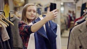 愉快的年轻女性客户试穿一件礼服并且采取与它的selfie在服装店的智能手机照相机 股票录像