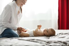 愉快的年轻妈妈在轻的卧室微笑和打扮她早晨步行的珍贵的男婴在公园 闩上构成概念系列螺母 库存照片