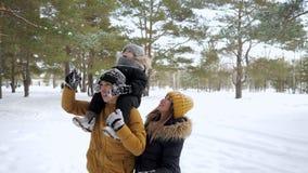 愉快的年轻家庭在冬天城市公园一起走 股票视频