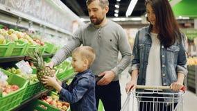 愉快的年轻家庭母亲、父亲和孩子在投入菠萝的超级市场买果子在购物车,谈话 股票视频