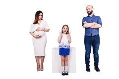 愉快的年轻家庭被隔绝在白色背景 有胡子的父亲、怀孕的母亲和愉快的女儿 免版税图库摄影