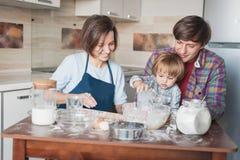 愉快的年轻家庭面团为曲奇饼做准备 免版税库存照片