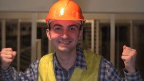 愉快的年轻工人或工程师或者建筑师,庆祝他的在建造场所的人成功 股票视频