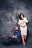 愉快的年轻怀孕的夫妇在黑暗的背景的演播室 家庭关系概念 免版税库存照片