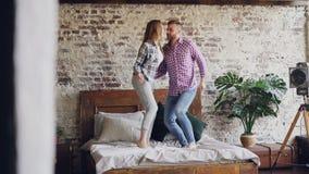愉快的年轻恋人在粗心大意地笑的双人床上跳舞获得乐趣在卧室和 快乐的人民,现代 影视素材