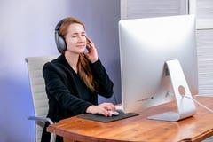 愉快的年轻成功的女实业家画象在办公室 她坐在与耳机的桌上并且看显示 免版税库存图片