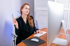 愉快的年轻成功的女实业家画象在办公室 她坐在桌上,拿着她的玻璃并且看二 库存图片