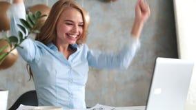 愉快的年轻成功的女实业家画象庆祝某事与胳膊 愉快的妇女在办公室坐并且看 股票录像