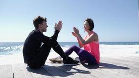 愉快的年轻打高五拍的比赛的男朋友和女朋友坐在海滩附近 飞溅反对岩石的波浪 股票视频