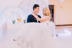 愉快的年轻新娘和新郎在婚礼大厅里跳舞 库存照片