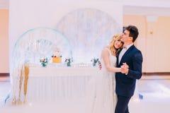 愉快的年轻新娘和新郎在婚礼大厅里跳舞 免版税库存照片