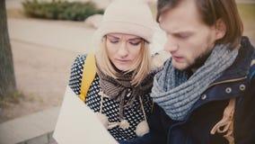 愉快的年轻旅游白种人男人和妇女失去的温暖的冬天衣裳的,一起看城市地图旅行指南 股票录像