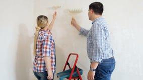 愉快的年轻有漆滚筒的夫妇绘的墙壁录影在他们在整修下的新的公寓 股票视频