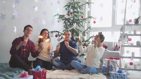 愉快的年轻朋友在装饰的屋子里烧闪耀叮当声香槟庆祝新年在美好的圣诞节旁边 股票视频