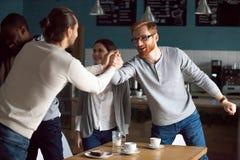 愉快的年轻朋友招呼在友好的会议上在咖啡馆 库存照片