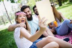 愉快的年轻朋友有乐趣外部本质上,采取selfie 免版税库存图片