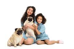 愉快的年轻母亲和女儿坐与两个可爱的哈巴狗的地板 图库摄影