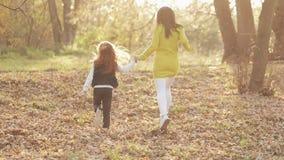 愉快的年轻母亲和她的小一起跑在秋天公园的红头发人女儿 他们笑和获得乐趣 股票录像