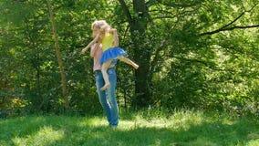愉快的年轻母亲画象桃红色打旋衬衣和的牛仔裤的整理和她微笑的小女儿在公园 影视素材