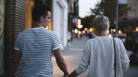 愉快的年轻浪漫夫妇在背景中握走沿平衡的手伦敦苏豪区,纽约,被弄脏的街灯 股票视频