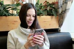 愉快的年轻深色的妇女认为事有趣并且聊天她的在咖啡馆的手机 图库摄影