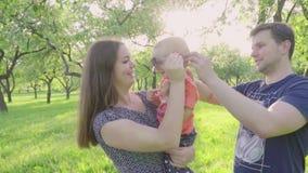 愉快的年轻父母份额亲吻他们逗人喜爱的男婴户外在公园 慢的行动 股票视频