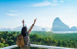 愉快的年轻由天空决定的旅客妇女背包徒步旅行者被举的胳膊享用 免版税库存图片
