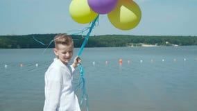 愉快的年轻男孩摆在与在湖的岸的五颜六色的气球 4K 股票视频