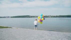愉快的年轻男孩站立与在湖的岸的五颜六色的气球 4K 股票录像