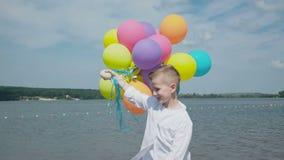 愉快的年轻男孩走与在湖的岸的五颜六色的气球 4K 股票视频