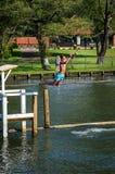 愉快的年轻男孩跳到泰晤士河在镇Henley附近在牛津郡 免版税库存照片