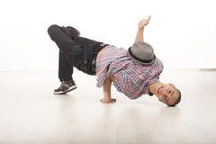 愉快的年轻男性舞蹈家坐他顶头微笑 库存照片