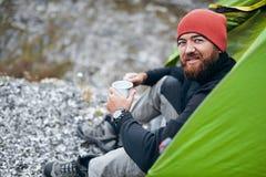 愉快的年轻男性饮用的热的饮料背面图在山的 有戴红色帽子的胡子的旅客人,坐近对野营 免版税库存照片