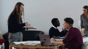 愉快的年轻白肤金发的上司女商人刺激的男性经理在现代办公室桌,不同种族的工作者上在背景中 影视素材
