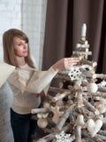 愉快的年轻白肤金发的女孩装饰一棵圣诞树 库存照片
