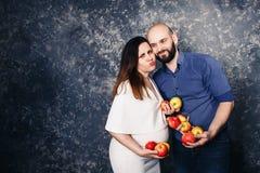愉快的年轻素食主义者家庭 拿着苹果和做滑稽的面孔的一个怀孕的女孩和一个有胡子的人在他们的手上 免版税库存照片