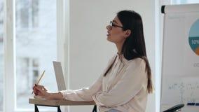 愉快的年轻美丽的典雅的女性白种人企业教练讲话在现代轻的coworking的办公室训练研讨会 股票录像