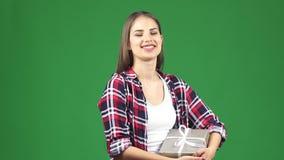 愉快的年轻美丽的妇女微笑的挥动对拿着礼物的照相机 影视素材